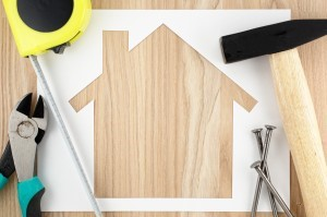 Home planning and preparing.House shaped paper cutout and tools on wood lumber.